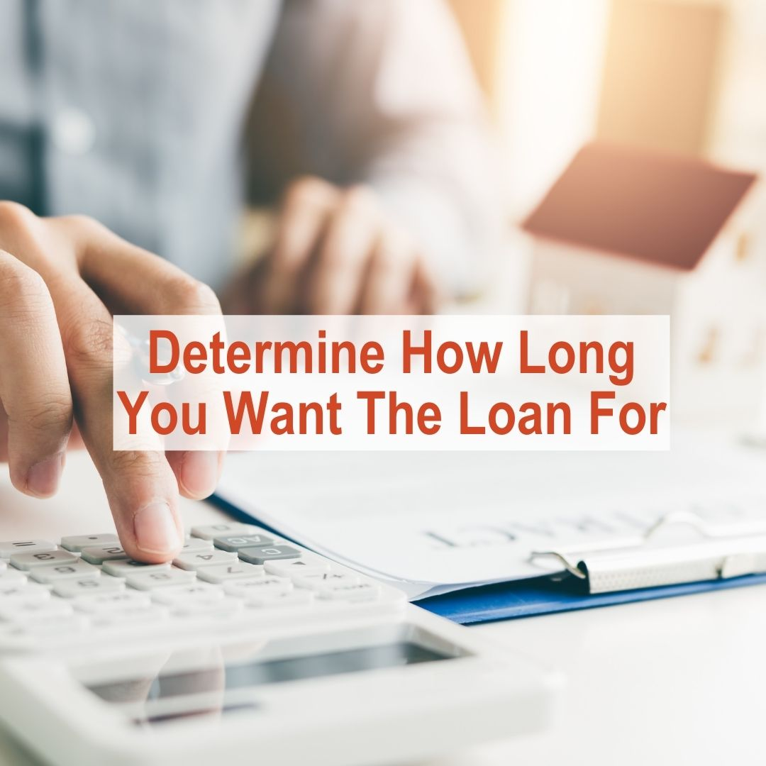 Person typing on a calculator at desk | Determine How Long You Want The Loan For