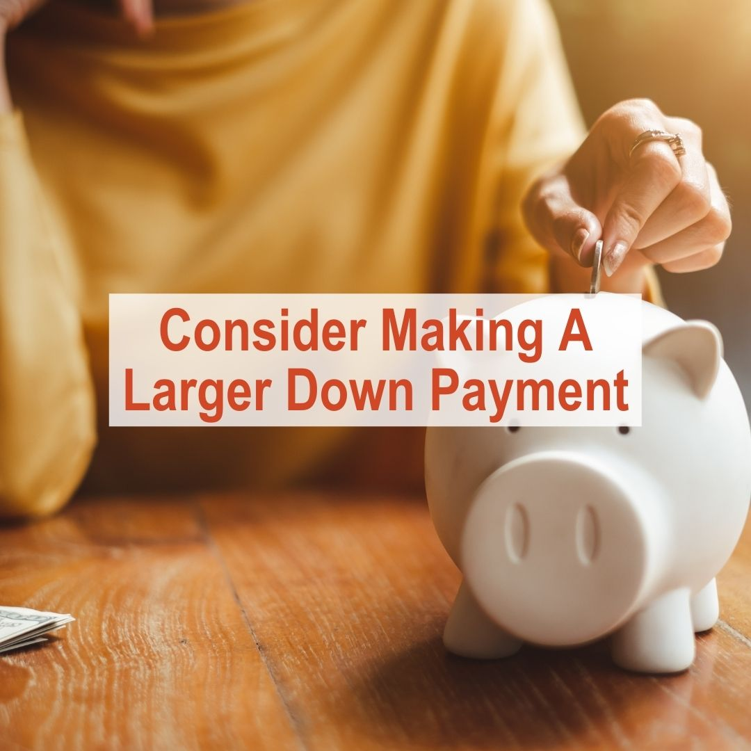 Woman putting quarter into piggy bank | Consider Making A Larger Down Payment
