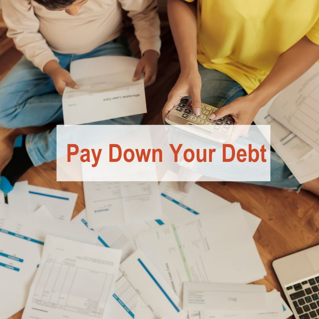 Two people sitting on floor with papers everywhere holding a calculator | Pay Down Debt