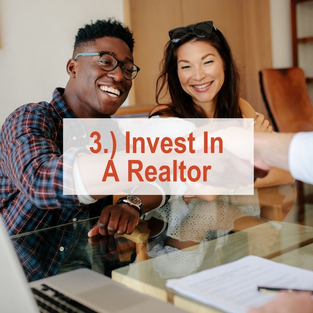 an African American man and asian woman holding up keys | Invest In A Realtor