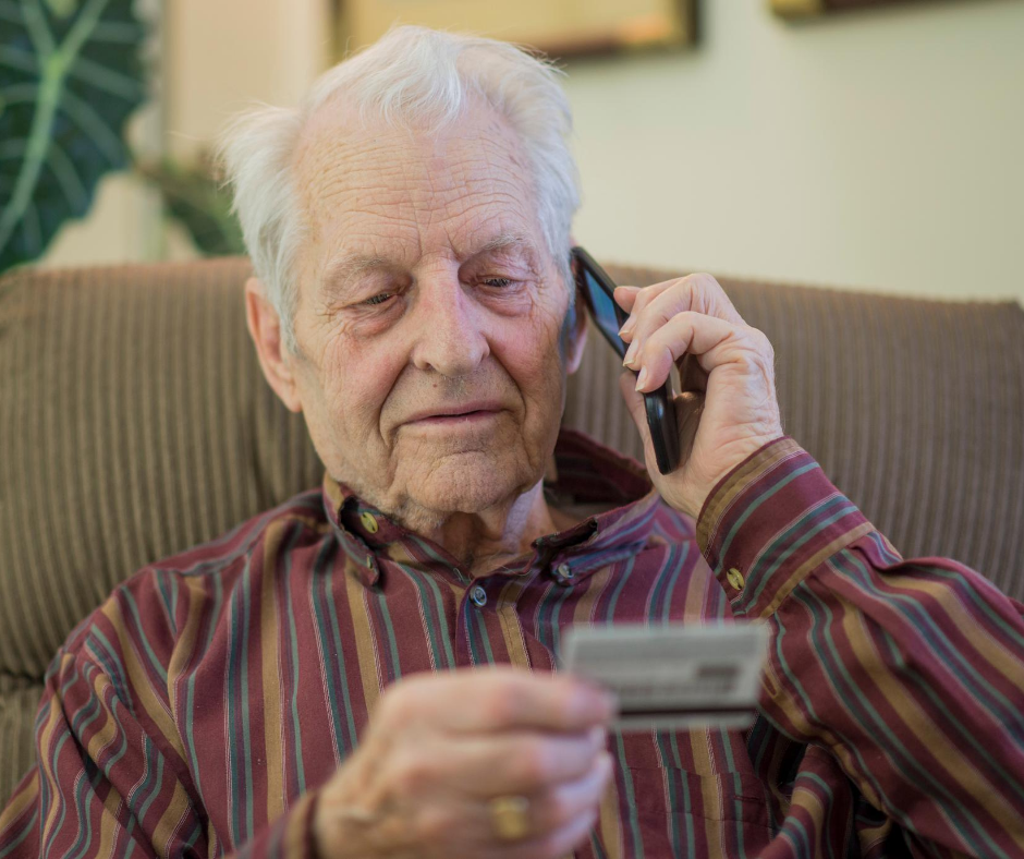 Elderly man talking on phone holding credit card
